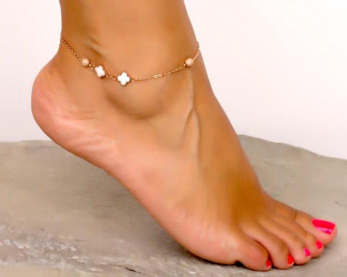 bracciale in oro sulla gamba con ciondoli